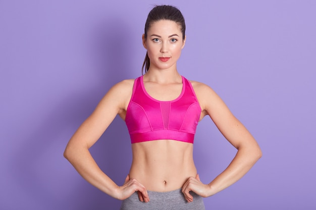 Winsome caucasian woman with pink workout clothing and ponytail