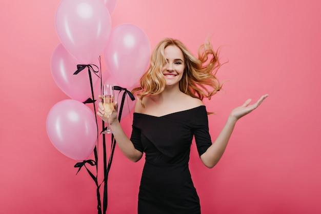 誕生日を祝うウェーブのかかった髪の魅力的なヨーロッパの女の子。パーティーで踊るヘリウム気球を持つかわいい若い女性。