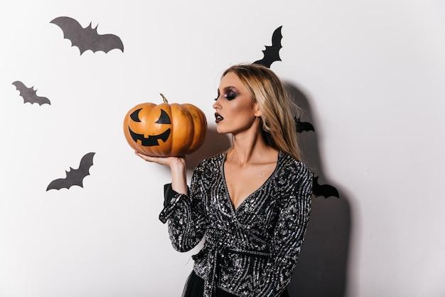 Обаятельная светловолосая дама держит тыкву на хэллоуин. фотография в помещении замечательной девушки в праздничном платье, готовящейся к карнавалу.