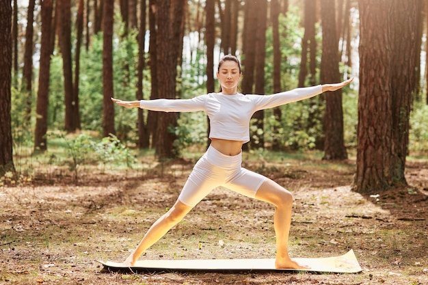 Winsome female in white sportswear practicing yoga in green park or forest, standing in yoga position, keeping eyes closed, spreading hands aside, training outdoor.