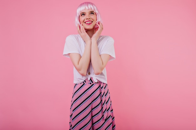 かつらのピンクの壁にポーズをとる機嫌の良い女の子。写真撮影中に微笑んで華やかな服装で陽気なヨーロッパの女性の屋内写真