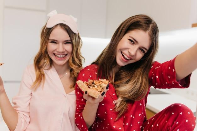 親友とのパーティー中に自分撮りを作る赤いナイトスーツのウィンサムガール。ピザを食べて笑っている2人の若い女性の屋内写真。
