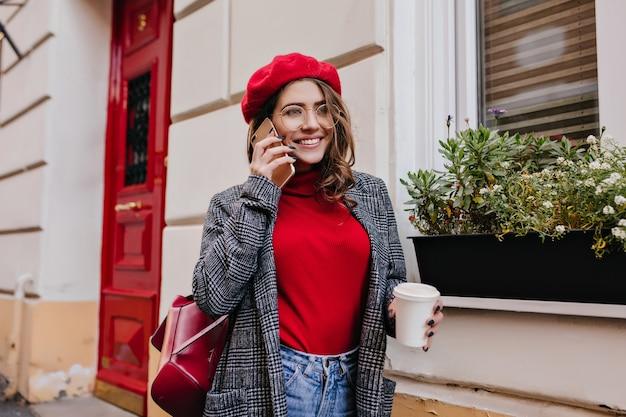電話で話し、カフェを通り過ぎて歩いているスタイリッシュなカジュアルな服装の魅力的な女の子