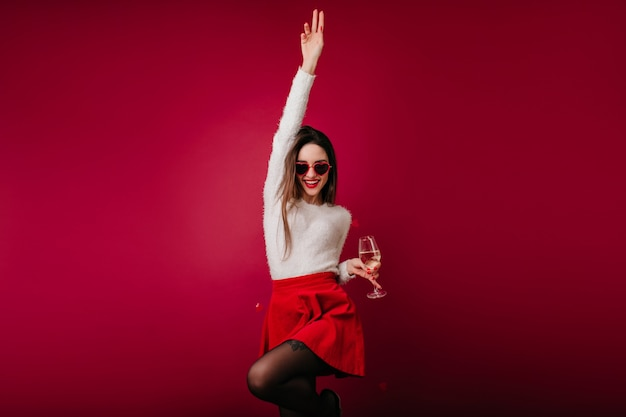 Winsome girl in short red skirt funny dancing with wineglass in hand