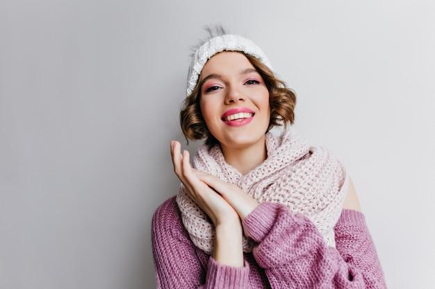 明るい壁にニットの冬のアクセサリーでポーズをとるピンクのメイクのウィンサムガール。帽子とスカーフで熱狂的な短髪の女性の屋内写真。