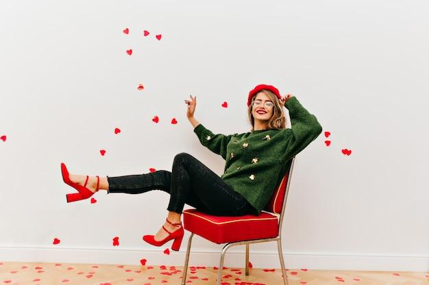 Красивая дама в очках веселится в студии, украшенной сердечками