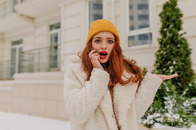 寒い日に電話で話している暗いウェーブのかかった髪の魅力的な女性。素晴らしい生姜の女の子の冬の肖像画。