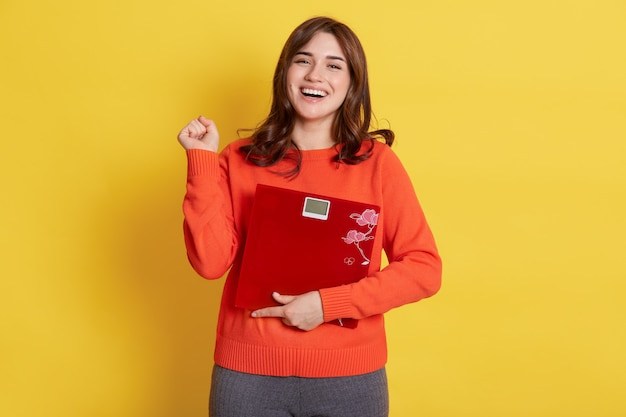 Winsome lady with floor scales in hands posing over yellow, clenching fist, being glad to slim down, finely loosing weight, girl wearing casual attire.