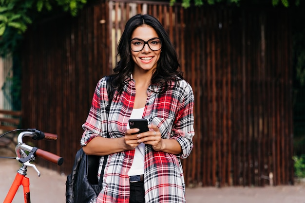 Winsome latin woman with happy smile holding smartphone on street. gorgeous european girl in casual outfit standing near bicycle.
