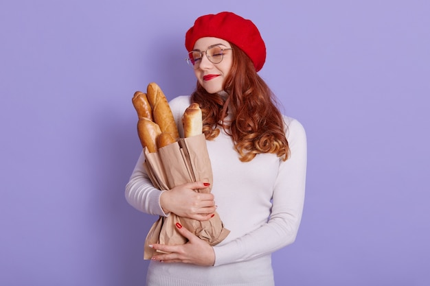 Winsome red haired young woman holding paper bag with bread on lilac space