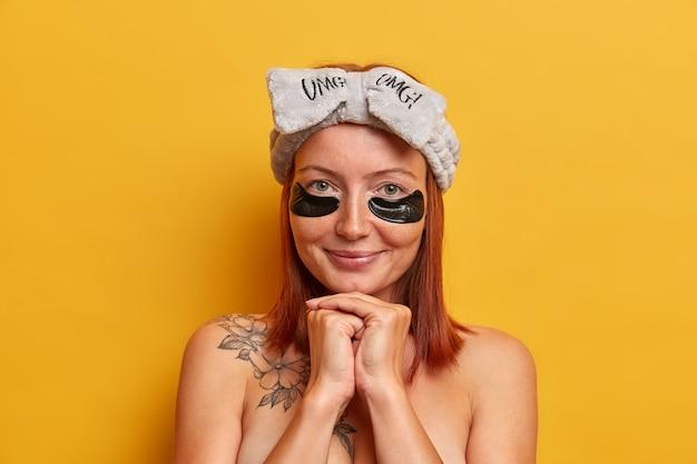 Accattivante femmina adulta dai capelli rossi tiene le mani unite sotto il mento, sorride delicatamente, applica cerotti di bellezza sotto gli occhi per l'idratazione e la calma della pelle, indossa la fascia per capelli con fiocco, spalle nude, tatuaggio