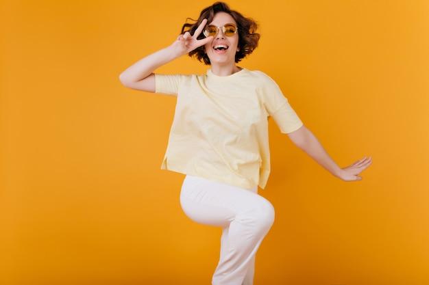 Ragazza dai capelli corti accattivante in abito bianco che balla sullo spazio arancione