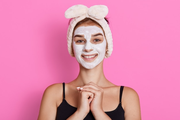 Winsome smiling brunette woman in funny hairband on head applying white nourishing mask or creme on face isolated over wall, keeps hands together in front of chest.