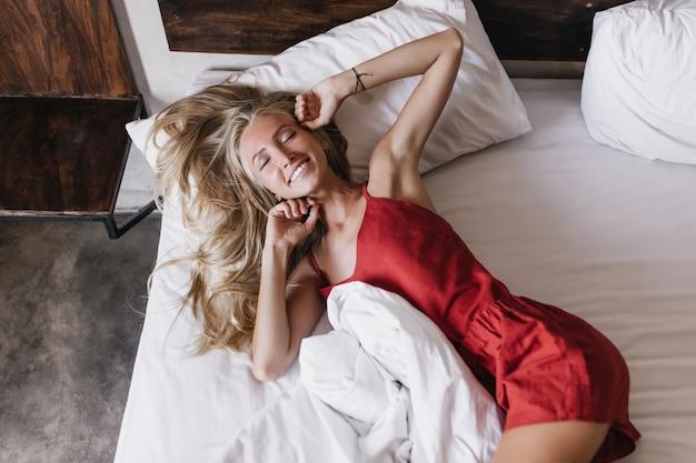 눈으로 침대에 누워 winsome 웃는 여자가 닫힙니다. 사랑스러운 긴 머리 금발의 여자가 이른 아침에 오싹하고 있습니다.