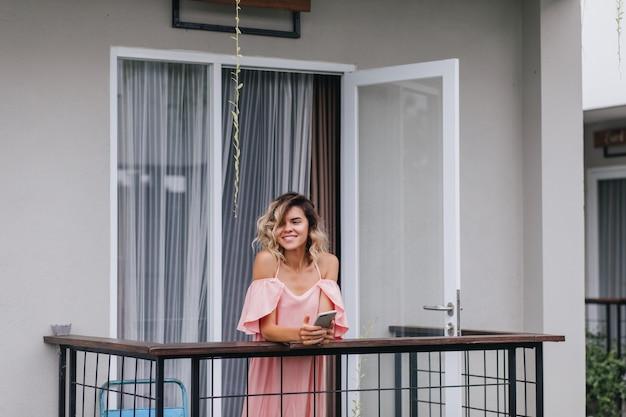 笑顔で目をそらしている手に携帯電話を持った魅力的な日焼けした女の子。ホテルのバルコニーに立っているピンクの衣装で陽気な若い女性。