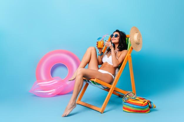 Donna abbronzata accattivante che si siede sulla sedia a sdraio con un bicchiere di succo di frutta