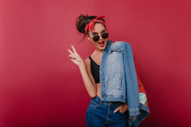 Winsome trendy lady in stylish sunglasses having fun during indoor photoshoot