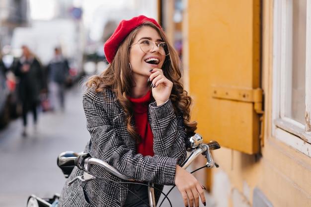 Accattivante ragazza bianca che guida la sua bicicletta per la città