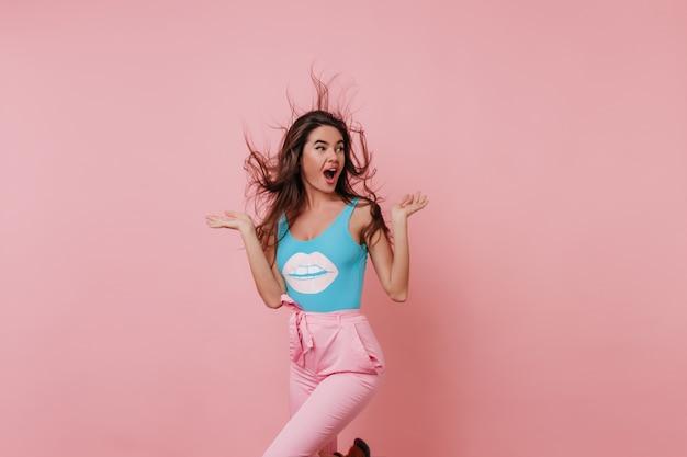 Divertente ragazza bianca accattivante che balla sullo spazio rosa