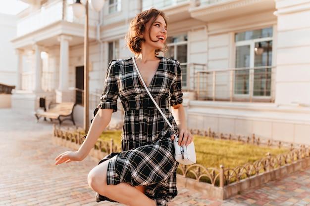 暖かい秋の日に歩き回る市松模様のドレスを着た魅力的な白人の女の子。巻き毛の茶色の髪を持つ壮大な女性の肖像画。