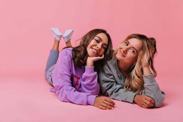 Симпатичные белые дамы лежат на полу с улыбкой. симпатичные подруги расслабляются с розовым интерьером.