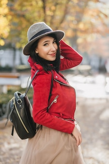 Winsome woman in bright red jacket looking over shoulder during walk in autumn park
