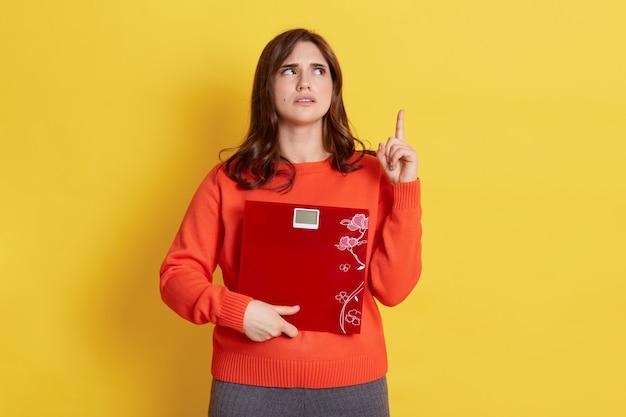 体重計を手に持ち、人差し指で見上げて上向きになり、黄色の上に立って、飛行機のスリム化方法を考えている魅力的な女性。