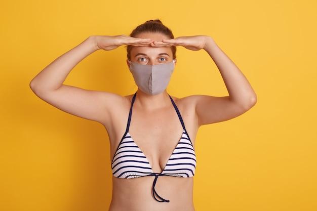 水着とメディカルマスクのハンサムな女性が黄色の壁にポーズをとって、両手のひらを額の近くに保ち、遠くを見ながら、隔離中に保護マスクを着用します。