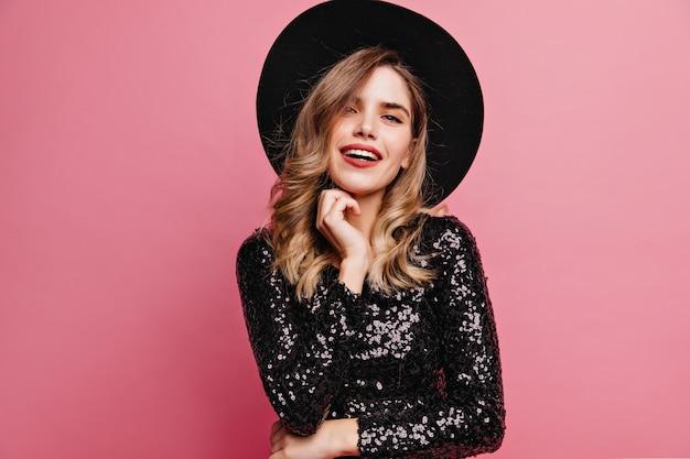 彼女のあごに触れているエレガントな帽子の魅力的な女性。ピンクの壁に分離された優雅な白人の女の子の屋内の肖像画。