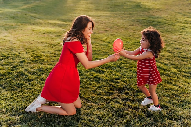 Winsome woman in red dress playing with her daughter in park. outdoor photo of laughing young lady looking at little sister with smile.