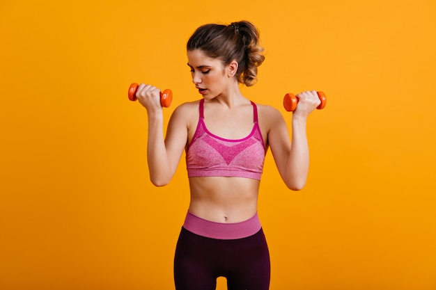 Winsome woman training with dumbbells