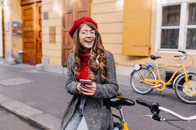 Donna accattivante in cappotto di tweed alla moda che guarda lontano con una risata davanti alla casa gialla