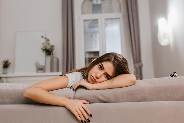 Обаятельная женщина с грустным выражением лица смотрит в камеру, лежа на удобном диване