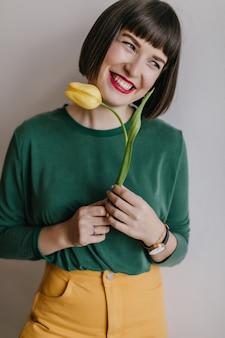 Donna accattivante con capelli scuri corti in posa con tulipano giallo. ritratto dell'interno della ragazza entusiasta in camicia verde che tiene fiore e che ride.
