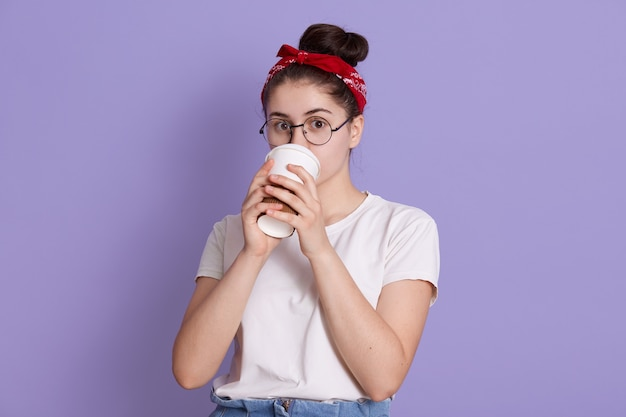 Winsome young happy beautiful woman in red hairband and white casual t shirt, poses against lilac space, drinking coffee in paper cup