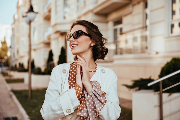 暖かい秋の日を楽しんでいるエレガントなサングラスをかけた魅力的な若い女性。白いジャケットを着た陽気な巻き毛の女の子の屋外ショット。