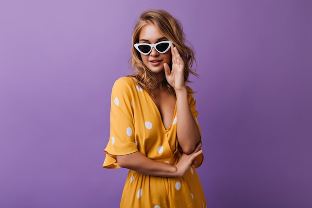 Winsome young woman playfully touching her sunglasses. indoor portrait of happy curly girl isolated on purple.