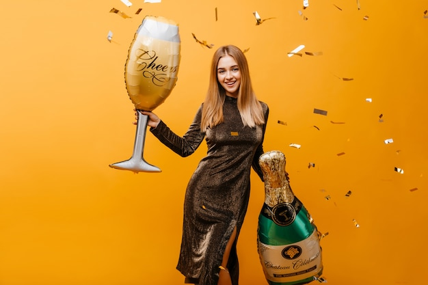 Winsome young woman with happy face expressiin waiting for birthday party. indoor portrait of shapely fair-haired woman with bottle of champagne and wineglass.
