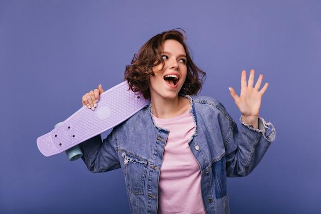 스케이트 보드와 함께 포즈 예쁜 미소로 winsome 젊은 여자. 짧은 물결 모양의 머리 서와 함께 웃고 평온한 아가씨의 실내 샷.