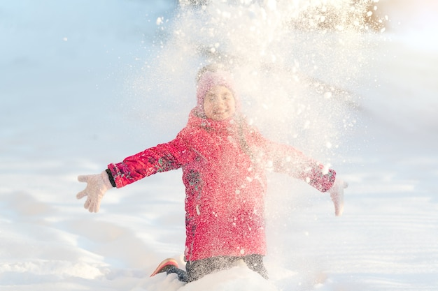 冬、女の子が雪を投げて外で遊ぶ