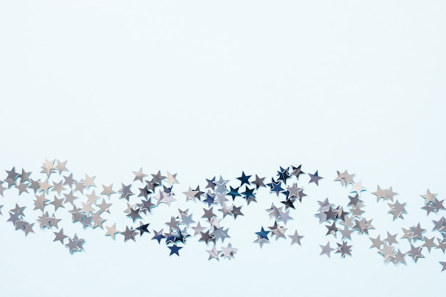 Winter abstract backround with silver foil confetti stars on blue
