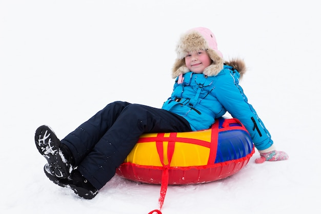 Winter active fun - happy girl ride from the snow hill on tubes