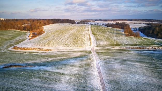 Winter agricultural field under snow. aerial scene. december rural landscape. countryside road top view. minsk region, belarus