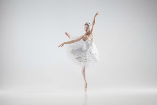 겨울은 살아있다. 젊은 우아한 클래식 발레리나 흰색 스튜디오 배경에 춤. 하얀 백조처럼 부드러운 옷을 입은 여자. 은혜, 예술가, 움직임, 행동 및 움직임 개념. 무중력 보인다.