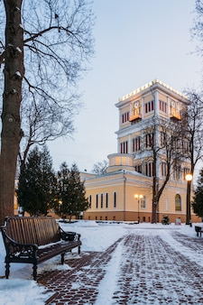 Winter alley with a bench and a clock tower in the park