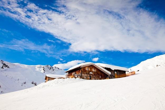 Winter in alps mountains, mayerhofen resort. wooden house under snow