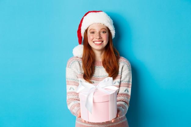 冬とお祝いのコンセプト。メリークリスマスを願って、贈り物を与えて、笑顔で、青い背景の上に立っているサンタ帽子の美しい赤毛の女の子。