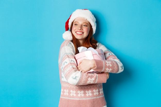 겨울과 축하 개념. 그녀의 크리스마스 선물을 포옹 하 고 찾고 왼쪽, 행복 하 게 웃 고, 파란색 배경 위에 서있는 산타 모자에 꿈꾸는 빨간 머리 소녀.