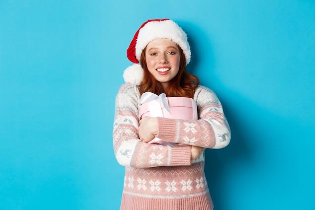 겨울과 축하 개념. 그녀의 크리스마스 선물을 포옹 산타 모자에 꿈꾸는 빨간 머리 소녀 행복 미소, 파란색 배경 위에 서.