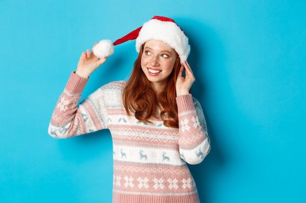 冬とクリスマスイブのコンセプト。サンタの帽子とセーターを着て、クリスマスを祝って、幸せそうに笑って、青い背景の上に立っているかわいい10代の少女。